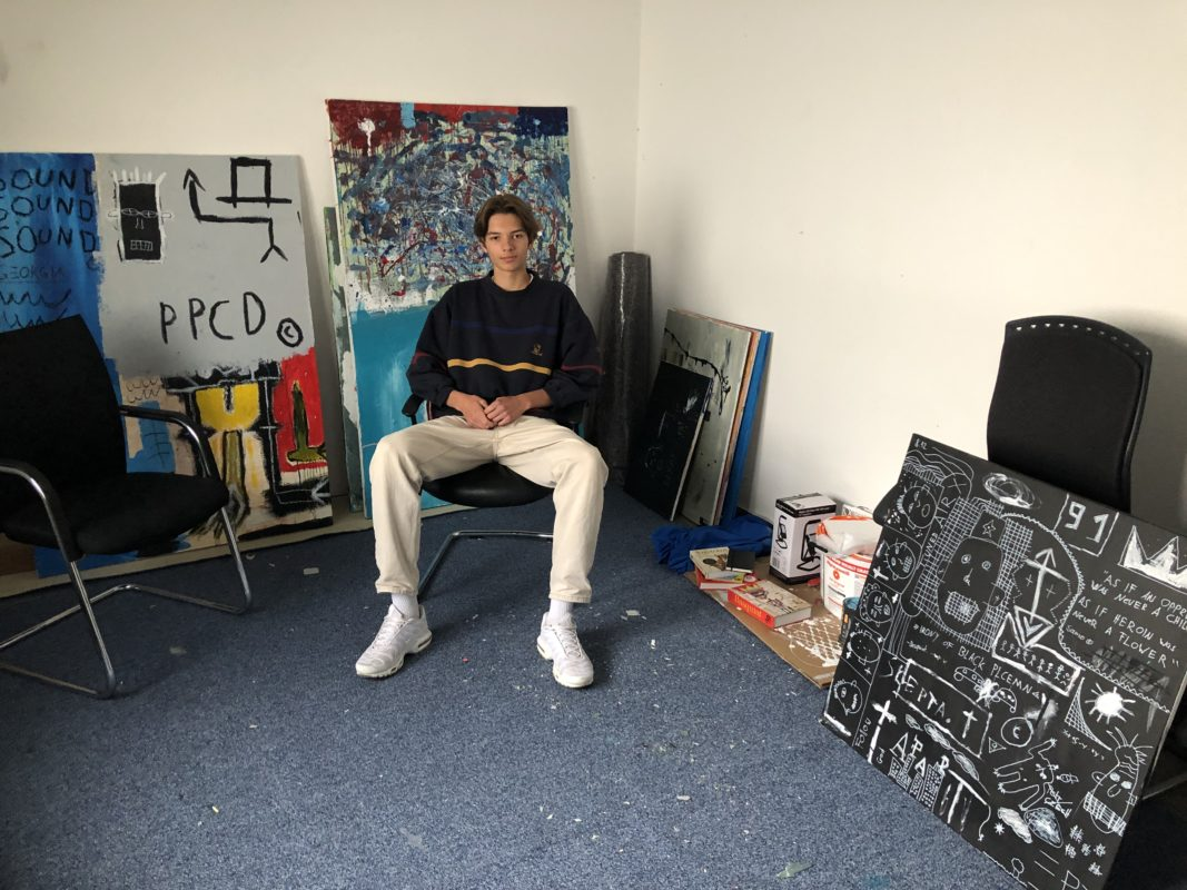 Der Künstler Tim Grieshaber in seinem Atelier vor seinen Kunstwerken
